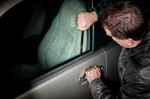 A male car thief uses a flat metal lock pick to break into a veh